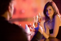 Young couple sharing champagne glasses in restaurant, celebratin